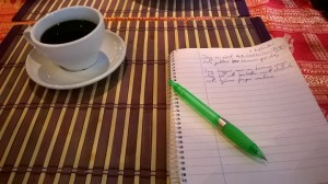 Picture of a cup of awesome coffee and writing pad.