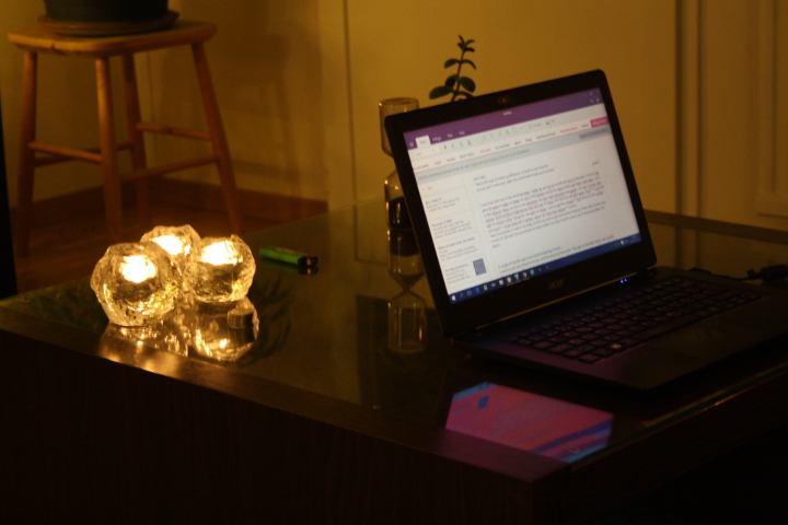 Picture of my laptop and candlelights in the early morning